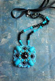 Soutache handmade pendant in black and turquoise colors. This beautiful, stylish pendant beneath any woman.  FREE SHIPPING  As a talisman, turquoise should be worn to attract health, love , success , prosperity . Travelers just need to take this stone on the road - it will take them from the dangers of the way , will make the journey easier and more enjoyable.  Pendant made ​​in technology soutache with crystal stones , turquoise beads, turquoise beads, seed beads. The back side is sewn…