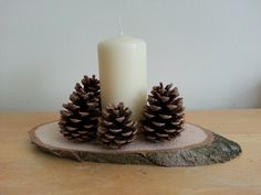 rustic wedding centrepiece with wooden slices, pine cones and a large candle