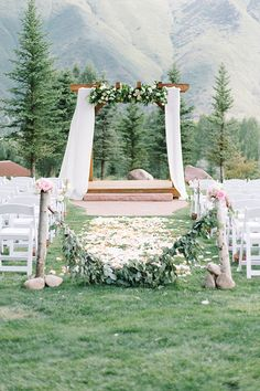 An outdoor wedding ceremony decked out with flowers and petals | @kateholstein | Brides.com
