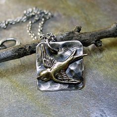 A sweet brass bird soaring across a silver sky.  from Lavender Cottage Jewelry on Etsy