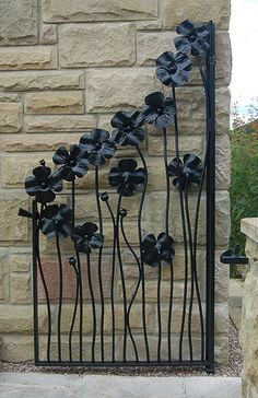 Isn't this lovely. Adrian's clients had bought some individual forged poppy heads and asked if the design could be incoporated into a garden gate. Using the flower head as the basis of the design, adding seed heads and a seed head latch - this is what Adrian came up with. I love the fact that there's no obvious top rail - careful design means that the flower heads are also structural.