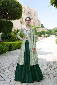 Magnify the wedding pageant by adorning this dress in bottle green and pista color. This dress is designed with pristine all over embroidery and lace work. The dress comes with bhagalpuri top and bhagalpuri bottom with sparkling chiffon dupatta.