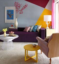 """Geometria assinada. A pintura geométrica da parede foi sugerida pelo designer de interiores Moreno. Esboçadas à mão, linhas diagonais foram pensadas para realçar os móveis de design e também para chamar a atenção de quem chega. """"Usei cores mais escuras em cantos periféricos para não afunilar a sala"""", diz o designer. Na porção maior, cor azul acinzentado Pico de Neblina, da Coral. Os tons de vinho e amarelo são, respectivamente, Framboesa Silvestre e Explosão de Estrela, da mesma marca."""