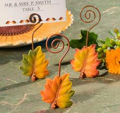 These Leaf Place Card Holders will add color and style to your Fall/Autumn wedding or special event. Features a dramatic poly resin fall leaf design in three assorted vivid fall colors and is embellished with three sparkling amber rhinestones on its stem. Each place card includes a fall themed place card.