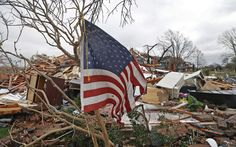 A tattered U.S. flag that had been attatched to a tree waves over the debris in Garland, Texas. A meteorolocical assault of tornadoes, blizzards and heavy rain have left dozens dead and a large path of property damage in the Central, U.S.