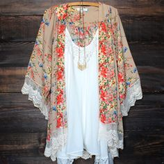 Beautiful opaque floral printed kimono with scallop crochet lace hem. Makes the perfect beach cover up! Shown with our flower child in ivory and chevron necklace. Sold separately. imported.