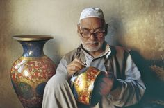 Rang7 myIndia An artisan working on a paper mache vase with traditional Kashmiri designs.