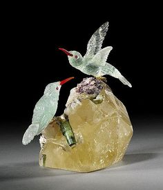 MATING PAIR OF AQUAMARINE HUMMINGBIRDS on TOURMALINE BASE<br>Artist: Peter Mueller<br>Brazil<br>This mating pair of Aquamarine hummingbirds are conversing while sitting on a matrix of Quartz and Tourmaline. The male bird has just landed, with his wings outspread while the female sits with her wings folded. This gemstone couple both have Garnet eyes, Carnelian beaks and gold plated sterling silver feet.  Detailed down to the pin feathers by master lapidarist Peter Mueller. The overall height…