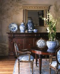 Beautiful blue and white upholstered dining chairs and ginger jars, with dark wood furniture.