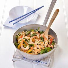 Roergebakken garnalen 400 g woknoedels 3 el wokolie 1 rode paprika 1 gele paprika 5 el geraspte kokos 2 el groene currypasta 300 g spinazie 1 limoen 150 g taugé 1 zak wokgarnalen 3 el gembersiroop