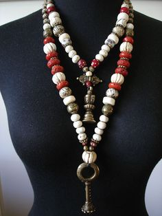 by Luda Hunter | Various Tibetan/ Nepalese shell beads including large old carved melon shell beads, Nepalese conch shell beads and lots of prayer beads inscribed with 'Om Mani Padme Hum'. Focal point in this longer tribal necklace is an old African Kirdi bronze bell dance pendant. Other beads include contemporary Nepalese sherpa coral beads, Ethiopian metal beads, old African flower brass beads, Nigerian brass beads and two bone beads