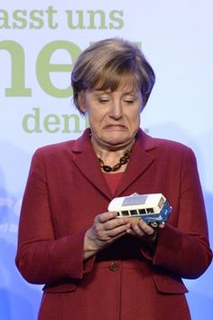 German Chancellor Angela Merkel holds a gift, a model Volkswagen during an election campaign rally in Munich.