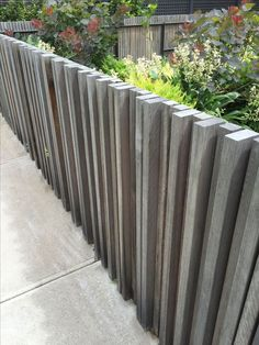 Summer style!! Really different and Interesting fence idea for outdoor gardens and yards - vertical layers of wood planks! Modern contemporary fence idea!