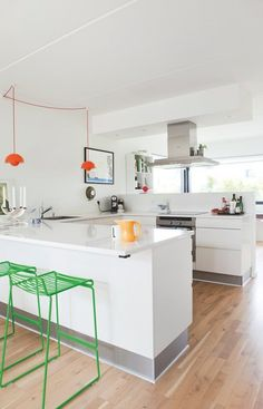 Striking colours create a funky atmosphere in the white HTH kitchen in Ceasarstone. The green bar stools are from Hay, and the 'FlowerPot' lamps are the original with fabric wires.