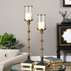 "Uttermost Santona Brass Candleholders, Set of 2 with Beige Candles Brushed, Brass Plated Metal Accented With Textured, Rust Black Details And Clear Glass Globes . Distressed Beige Candles Included. Sizes: Sm-6""x23""x6"", Lg-6""x27""x6"" Collection: Santona Designer: Billy Moon Material:..."