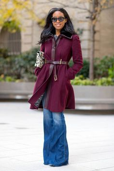 Woman wearing flared jeans, and an oxblood coat