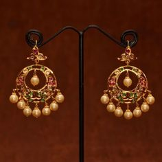 Chand bali studded with uncut stones, emeralds and rubies with pearl hangings