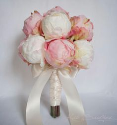 This ivory and blush pink peony wedding bouquet is romantic and elegant. Fifteen natural ivory and soft blush pink peony buds are hand-tied with ivory satin ribbon, braided and bowed. Each peony has s