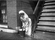 Maid mopping up the pavement. Amsterdam, the Netherlands, 1912.