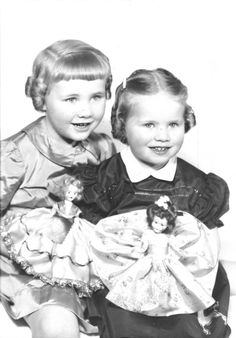 Vintage photo of two little girls posing with their dolls, circa 1950's.