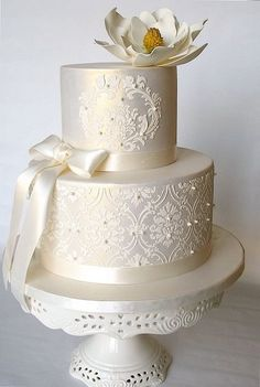 Ivory lustered wedding cake with stencilling, ribbon and flower