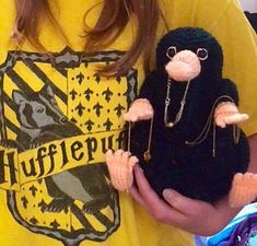 """I caught this little guy sniffing around under my bed, and discovered that all of my loose change had somehow """"accidentally"""" ended up in his pouch! At least he's good at holding onto my money for me. ESPECIALLY due to the fact that, unlike most niffler patterns out there, this one boasts a spacious tube hidden behind his pouch where many many coins can be stored, making dumping them out into a fun party trick just like in the film Fantastic Beasts and Where to Find Them!"""