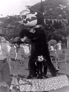 "Old,celluloid negative photograph of a large ""Felix the Cat"" Giant Doll or Felix Costume, and ""Felix the Cat"" toys of various sizes. Singapore,China. c1920s. Young Boy Scout standing by the Felix display."