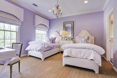 Shared purple girls' room features walls painted purple lined with a pair of white tufted twin beds dressed in purple bedding and pillows flanking a three drawer dresser with ring pulls and a crystal baluster lamp placed beneath a lattice mirror illuminated by a French candle chandelier. Girls Bedroom Colors, Girl Bedroom Walls, Girls Room Design, Bedroom Wall Colors, Girl Bedroom Designs, Bedroom Styles, Bedroom Ideas, Twin Girl Bedrooms, Little Girl Rooms