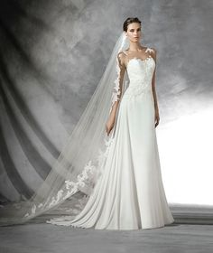 Flared gauze wedding dress with rebrodé lace, thread embroidery and gemstone appliqués. Bodice with sheer underbodice decorated with appliqués. Sheer back decorated with lace and plain gauze skirt.