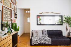 Sala de casinha antiga preserva elementos originais como o piso de madeira. Na decoração, as moradoras optaram pelo estilo industrial.