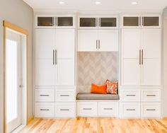 Floor-to-ceiling cabinets and drawers offer maximum storage to this mudroom. A built-in bench sits in the center of it all; the graphic wallpaper behind it and bright orange pillows bringing bold visual punch to the space.