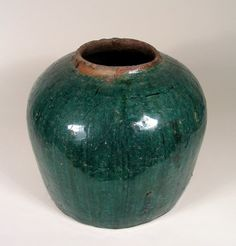 "A large Qing Dynasty pottery jar formed from red clay with a wide mouth and covered in a thick, crackled, dark teal-colored glaze. DIMENSIONS: 7 ¾"" high (19.5 cm) x 9"" diameter (22.8 cm)."