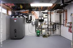 Mechanical systems view #1 solar thermal hot water storage tank (left), high-efficiency gas-fired boiler (right) / Vue #1 des installations ...