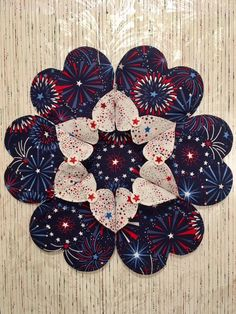 This is a festive, Patriotic, 4th of July heart to heart table topper, with folded hearts . It is created with a 100% cotton prints, featuring a 4th of July fireworks print for the larger hearts, and a contrasting a shimmering stars print, for the smaller hearts, which fold open.