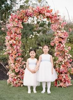 Flower girls in front of ceremony florals