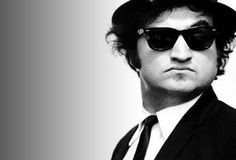 """John Belushi was an actor and comedian, one of the first performers on """"Saturday Night Live"""" and one half of the Blues Brothers. John Adams, Saturday Night Live, Recital, Looks Black, Black And White, The Blues Brothers, Fritz Lang, Ray Ban Sunglasses Sale, New Wave"""