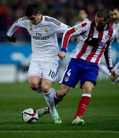 Mario Suarez (R) of Atletico de Madrid tackles James Rodriguez (L) of Real Madrid CF during the Copa del Rey Round of 16 first leg match between Club Atletico de Madrid and Real Madrid CF at Vicente Calderon Stadium on January 7, 2015 in Madrid, Spain.