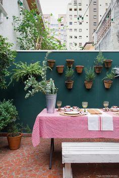 Quintal com parede pintada de verde e arranjo de vasinhos de barro