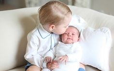 Prince George holds baby sister Princess Charlotte in family pictures taken by Kate Middleton