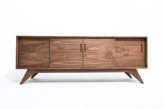 Our 80 storage credenza provides elegance and function. The inside of the cabinet is broken up into three sections: one large 38 wide compartment in the middle, and two 19.5 wide cubbies on the left and right. Each section has an adjustable shelf. Grain sequenced doors with routed finger slots slide side-to-side on natural wood and runners  Features: -solid hardwood base -superior quality veneered cabinet -adjustable shelving -natural wood door slides -grain sequenced doors that have been…