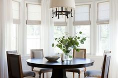 Bright dinning room with small table, upholstered chairs, and a plant