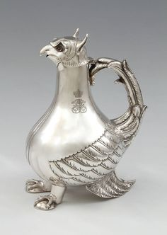 A Griffon-Shaped Silver Claret Jug Made in the Austro-Hungarian Empire, this expressive piece is based on a porcelain chocolate pot made in Vienna between 1744 and 1749, which in turn was most likely inspired by a 12th-century metal aquamanile in the Kunstshistorisches Museum in Vienna.  Maker's marks of A.B.A., Peste, c. 1870. Assay marks of Peste 1867-1872. 800.