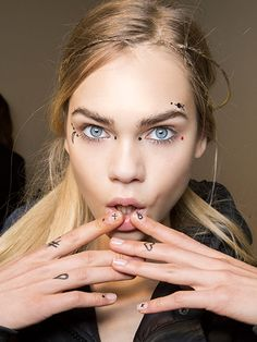 """For Giamba's fall show, manicurist Keri Blair made DIY nail decals by drawing shapes, like infinity symbols and hearts, on a ziplock bag with a nail-striping brush and black and red polish. Cover dried decals with topcoat, peel them off, place on nails, and add a layer of topcoat to keep them in place. —from """"Show of Hands"""" by Jenna Rosenstein"""