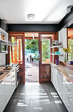 """A segunda porta de correr da cozinha conduz à área externa. """"De ipê, ela é mais resistente ao tempo"""", justifica a arquiteta.Os armários, feitos sob encomenda pela SCA, empregam laminado melamínico. Piso de porcelanato de 50 x 50 cm."""