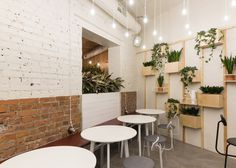 Baranova Pokorsky has transformed a Soviet-era furniture store into a vegetarian coffee shop, pairing simple materials with plant-lined shelves