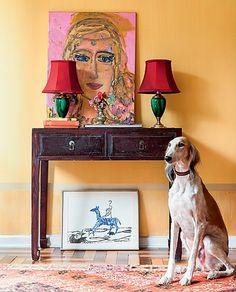 """Uma parede na cor amarelo-ocre foi capaz de transformar tudo ao redor. """"O tom é quente e luminoso"""", explica a pintora Verena Matzen. Por não ter medo de ousar, ela colocou sobre o aparador abajures que somam o verde e o vermelho e um autorretrato"""