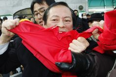 Plainclothes police officers try to stop a protester from tearing a Chinese flag with his teeth during an anti-China protest near the Chinese embassy in Seoul. (Reuters)
