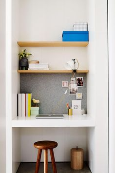 Small compact workspace nook: built-in wooden shelves and white desk, wooden stool, light grey fabric pinboard