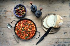 A large bowl of quick and easy Spanish Beans and Tomatoes (vegan and gluten free) with a bowl of olives.