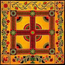 The cheddar color of Sue Nickels' folk art quilt is stunning